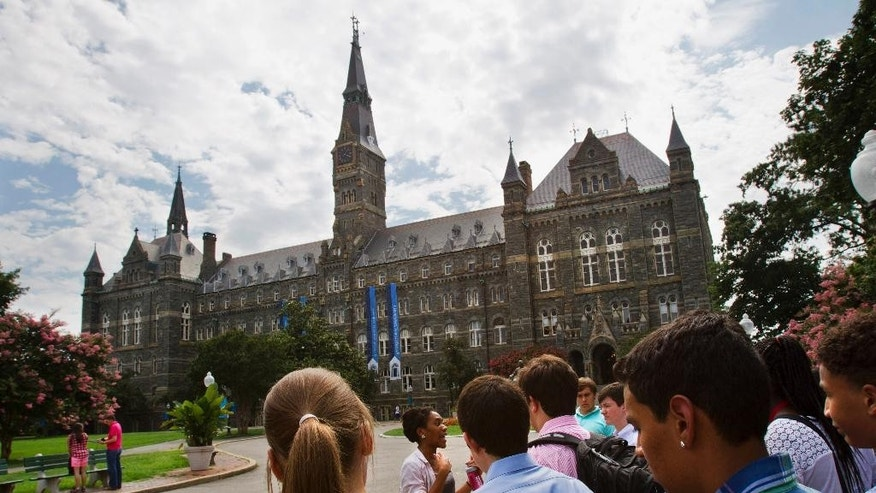 FILE - In this July 10, 2013, file photo, prospective students tour Georgetown University's campus in Washington. Georgetown University will give preference in admissions to the descendants of slaves owned by the Maryland Jesuits as part of its effort to atone for profiting from the sale of enslaved people, the president of the prominent Jesuit university in Washington announced Thursday, Sept. 1, 2016. (AP Photo/Jacquelyn Martin, File)