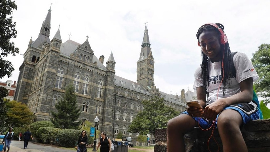 Deja Lindsey, 20, a junior at Georgetown University, talks on her cell phone in front of Healy Hall on campus, Thursday, Sept. 1, 2016, in Washington. After renaming the Mulledy and McSherry buildings at Georgetown University temporarily to Freedom Hall and Remembrance Hall, Georgetown University will give preference in admissions to the descendants of slaves owned by the Maryland Jesuits as part of its effort to atone for profiting from the sale of enslaved people. Georgetown president John DeGioia announced Thursday that the university will implement the admissions preferences. The university released a report calling on its leaders to offer a formal apology for the university's participation in the slave trade.  (AP Photo/Jacquelyn Martin)