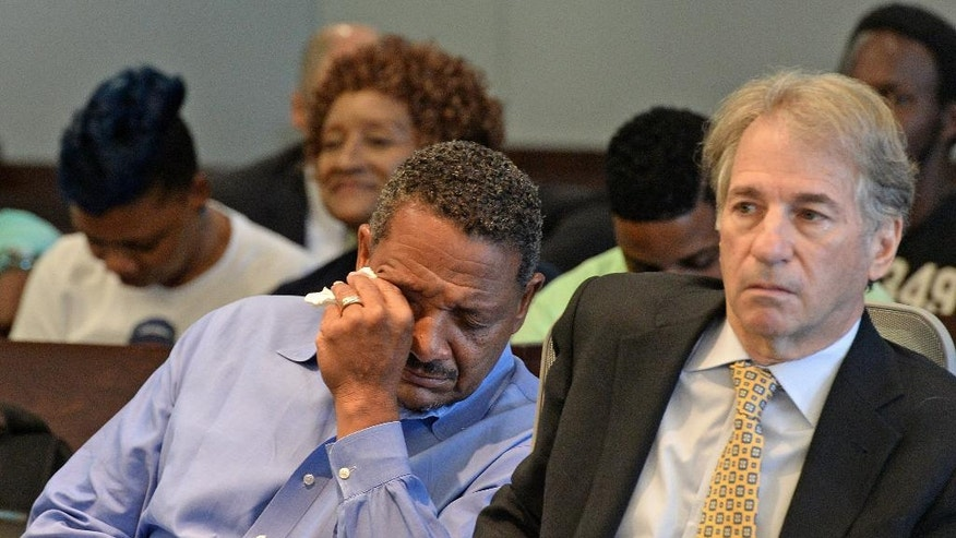 Darryl Howard, left, wipes away tears after Judge Orlando Hudson threw out Howard's double-murder conviction Wednesday, Aug. 31, 2016, in a Durham County Courthouse courtroom, in Durham, N.C.  The judge threw out the convictions and ordered Howard's release because of DNA evidence unavailable at Howard's 1995 murder trial. His lawyer, Barry Scheck, co-director of the N.Y. based Innocence Project, is at right. (Chuck Liddy/The News & Observer via AP)
