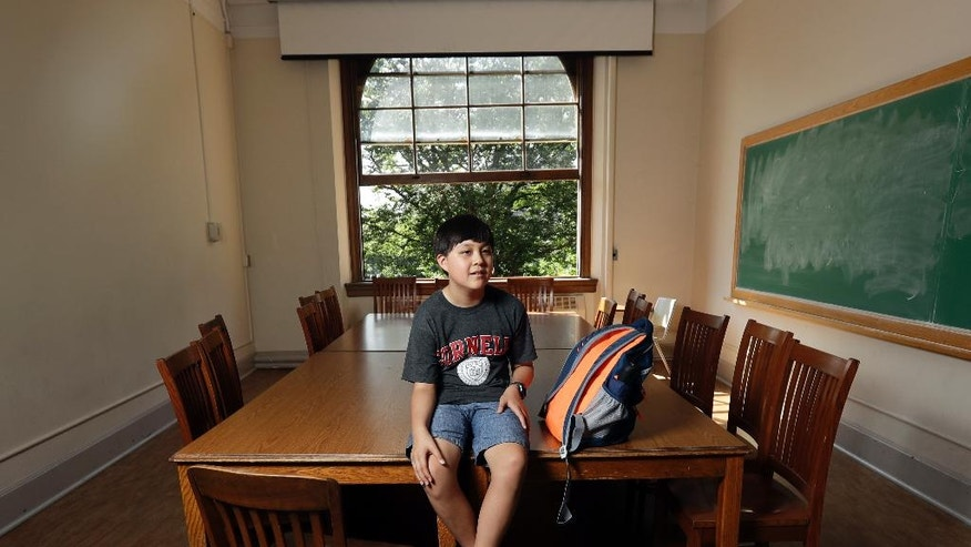 In this Friday, Aug. 26, 2016 photo, Jeremy Shuler, 12, a freshman at Cornell University, poses on campus in Ithaca, N.Y. He's the youngest student on record to attend the Ivy League school. Jeremy's parents, who are both aerospace engineers, moved from Grand Prairie, Texas, to Ithaca, New York, so he could live with them while pursuing his engineering degree. (AP Photo/Mike Groll)