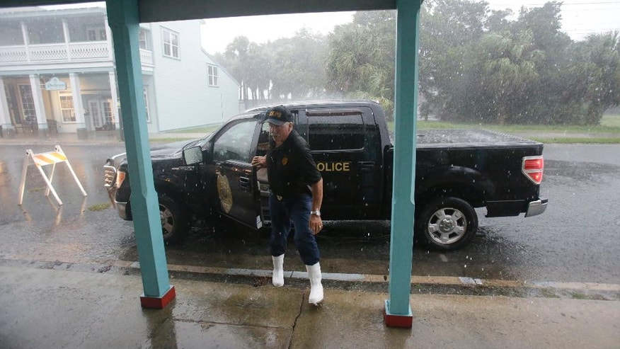 Cedar Key police chief Virgil Sandlin checks on the downtown area as Hurricane Hermine nears the Florida coast, Thursday, Sept. 1, 2016, in Cedar Key, Fla. Tropical Storm Hermine strengthened into a hurricane Thursday and steamed toward Florida's Gulf Coast, where people put up shutters, nailed plywood across store windows and braced for the first direct hit on the state from a hurricane in over a decade. (AP Photo/John Raoux)