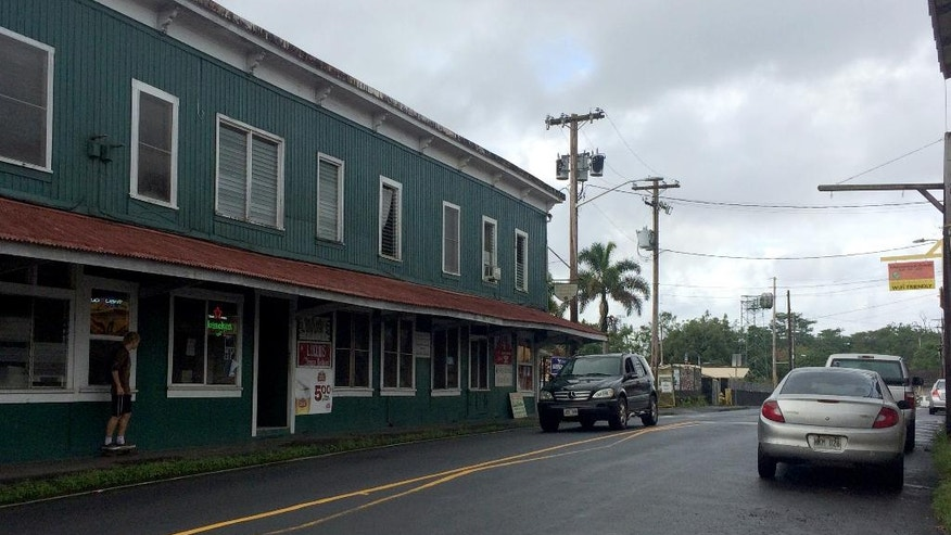 A man stands on a street in Pahoa, Hawaii after Tropical Storm Madeline moved through the area, Thursday, Sept. 1, 2016. The tropical storm left parts of Hawaii's Big Island soggy but intact as residents of the island state prepare for a second round of potentially volatile tropical weather. Hurricane Lester remains on track to impact the islands this weekend, but possibly after being downgraded to a tropical storm. (AP Photo/Audrey McAvoy)
