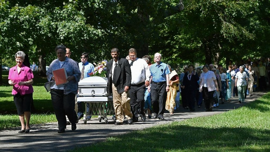 The casket containing the remains of Sister Paula Merrill, leads the processional into the cemetery following her funeral service, Friday, Sept. 2, 2016, at St. Vincent Church in Bardstown, Ky. Sister Merrill, with the Sisters of Charity of Nazareth and another nun were found murdered in their home on Aug. 25 in Durant, Miss. (AP Photo/Timothy D. Easley)