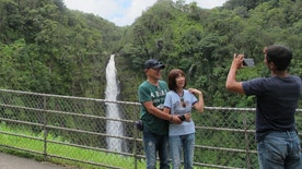 A couple poses for a photo at Akaka Falls in Honomu, Hawaii on Friday, Sept. 2, 2016. Tourists in Hawaii who had been planning an escape to a sunny island paradise were instead hit with the threat of back-to-back hurricanes, but they're making the best of their vacations. (AP Photo/Audrey McAvoy)