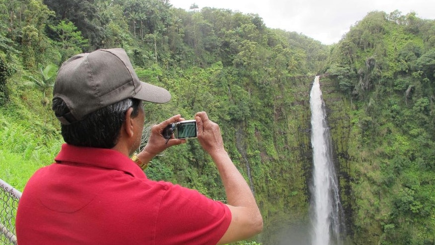 A man takes a photo of Akaka Falls in Honomu, Hawaii on Friday, Sept. 2, 2016. Tourists in Hawaii who had been planning an escape to a sunny island paradise were instead hit with the threat of back-to-back hurricanes, but they're making the best of their vacations. (AP Photo/Audrey McAvoy)