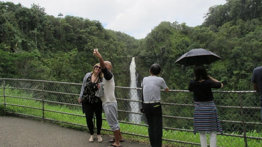 A couple poses for a selfie at Akaka Falls in Honomu, Hawaii on Friday, Sept. 2, 2016. Tourists in Hawaii who had been planning an escape to a sunny island paradise were instead hit with the threat of back-to-back hurricanes, but they're making the best of their vacations. (AP Photo/Audrey McAvoy)