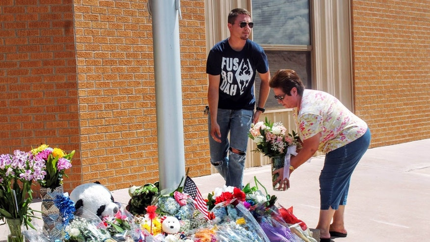 Sept. 2, 2016: Residents add to a sidewalk memorial outside Alamogordo, N.M., police headquarters.