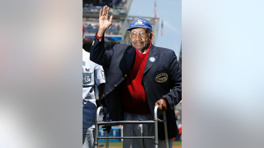 In this June 5, 2013 file photo, Tuskegee Airman Dabney Montgomery waves to the crowd as he is introduced before the start of a baseball game between the New York Yankees and the Baltimore Orioles in New York.