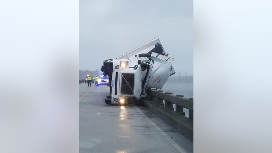 In this photo provided by Tyrrell County Sheriff's office shows a tipped over 18-wheeler in Columbia, N.C., on Saturday, Sept. 3, 2016.  Tyrrell County Sheriff Darryl Liverman said that high winds tipped over the 18-wheeler, killing its driver and shutting down the U.S. 64 bridge during Tropical Storm Hermine.   (Tyrrell County Sheriff's office via AP)