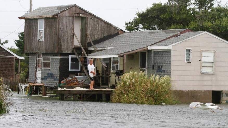 A unidentified man watches the rising water from his home in Hatteras, N.C., Saturday, Sept. 3, 2016 after Tropical Storm Hermine passed the Outer Banks.  The storm is expected to dump several inches of rain in parts of coastal Virginia, Maryland, Delaware, New Jersey and New York as the Labor Day weekend continues.  (AP Photo/Tom Copeland)