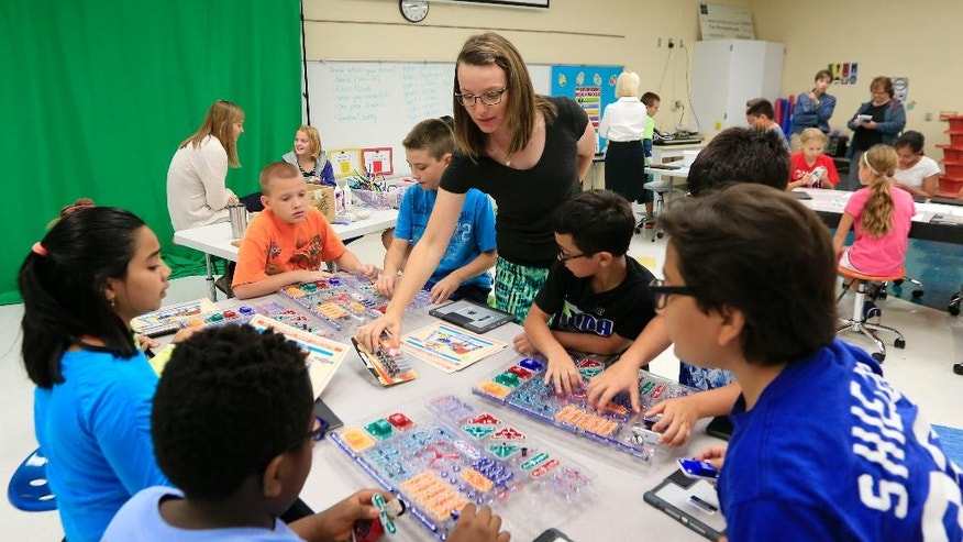 """Fifth grade teacher Suni Haberland provides batteries for a makerspace workstation at Bluejacket Flint Elementary School in Kansas City, Kan., Thursday, Aug. 25, 2016. The """"makerspace"""" movement sweeping through K-12 schools across the United States encourages collaborative, creative, student-driven education. But there are concerns about how already-busy teachers can incorporate a counterpoint to schools' increasingly test-based curriculums and emphasis on reading, writing and arithmetic.  (AP Photo/Orlin Wagner)"""