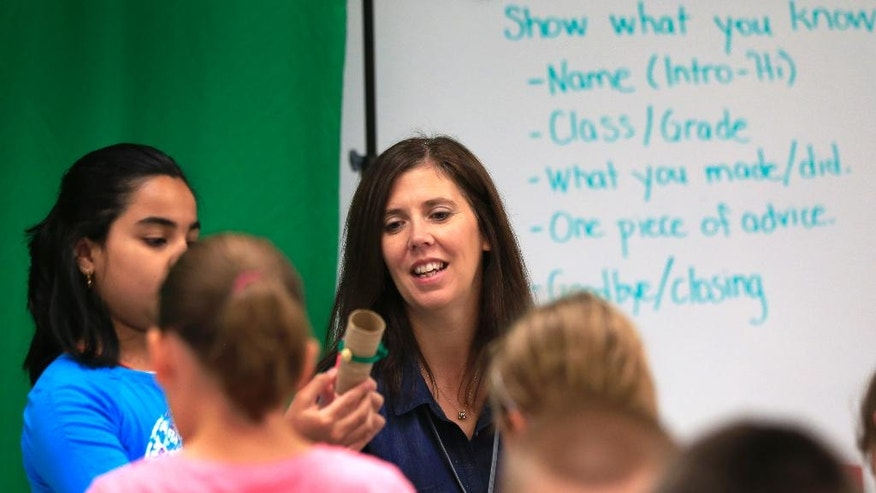 """Michelle Brown works with students in a makerspace at Bluejacket Flint Elementary School in Kansas City, Kan., Thursday, Aug. 25, 2016.  The """"makerspace"""" movement sweeping through K-12 schools across the United States encourages collaborative, creative, student-driven education. But there are concerns about how already-busy teachers can incorporate a counterpoint to schools' increasingly test-based curriculums and emphasis on reading, writing and arithmetic.  (AP Photo/Orlin Wagner)"""