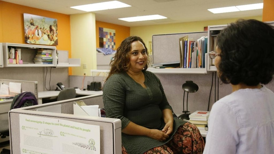 In this photo taken Friday, Sept. 2, 2016, Rajasvini Bhansali, left, executive director of the International Development Exchange, also known as IDEX, talks with a co-worker at her office in San Francisco. Black Lives Matter has quietly established a legal partnership with the California charity in a sign of the movement's growth and expanding ambition. The nonprofit charity also known as IDEX has been acting since November as a mostly unseen financial arm of Black Lives Matter, which two years ago grew out of street protests and a hashtag. (AP Photo/Eric Risberg)
