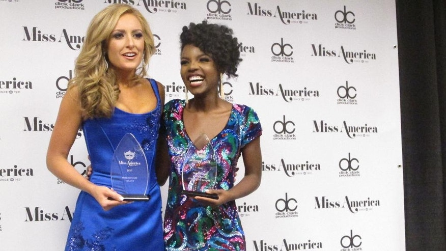"""Miss Tennessee Grace Burgess, left, and Miss District of Columbia Cierra Jackson, right, speak with reporters after winning preliminary competitions in the first night of the Miss America pageant in Atlantic City, Tuesday, Sept. 6, 2016. Burgess won the talent competition by singing The Eagles' """"Desperado."""" Jackson won the swimsuit competition. (AP Photo/Wayne Parry)"""