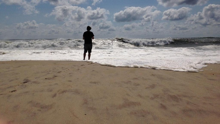 A beachgoer stands at the edge of the water, Sunday, Sept. 4, 2016, in Bridgehampton, N.Y., on the southeastern shore of Long Island, where the effects of storm system Hermine could be seen in the rough surf and a ban on swimming. Hermine spun away from the U.S. East Coast on Sunday, removing the threat of heavy rain but maintaining enough power to churn dangerous waves and currents and keep beaches off-limits to disappointed swimmers and surfers during the holiday weekend. (AP Photo/Jennifer Peltz)
