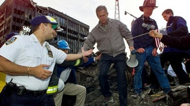 """FILE - In this Friday, Sept. 14, 2001 file photo, Joseph Esposito, left, chief of department of the New York Police Department, offers help as President George W. Bush steps off of a pile of rubble after speaking at ground zero of the World Trade Center site in New York. Esposito, then the NYPD's top uniformed officer, was struck by """"the camaraderie, the unity"""" of those days. (AP Photo/Doug Mills)"""