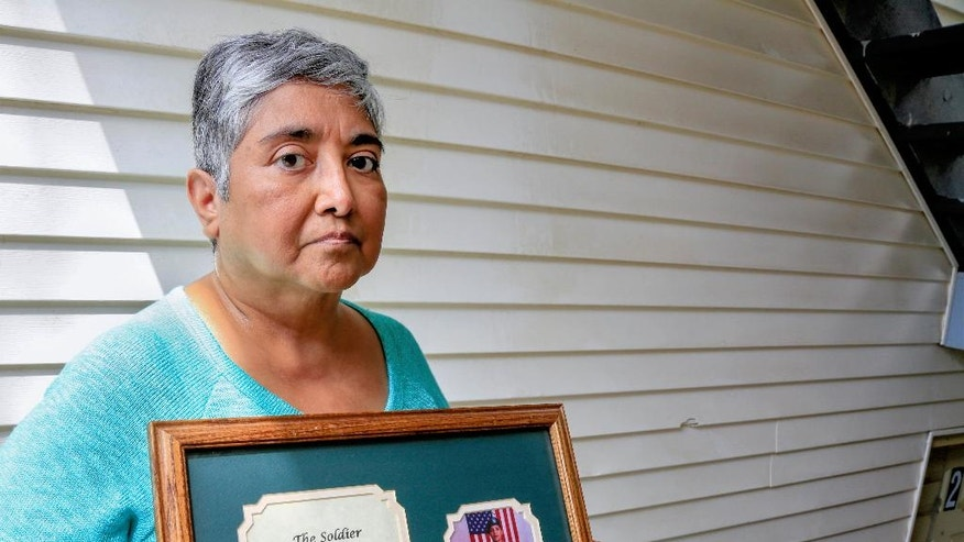 """Maria Medrano-Nehls, aunt and foster mother of Nebraska army guard Master Sgt. Linda Tarango-Griess, holds a photo of her in Lincoln, Neb., Thursday, Aug. 18, 2016. Tarango-Griess was killed by an IED in Iraq in 2004. In the wake of the Sept. 11, 2001 attacks, she recalls, """"I really saw people stand up for America. ... And I was very proud of that."""" (AP Photo/Nati Harnik)"""
