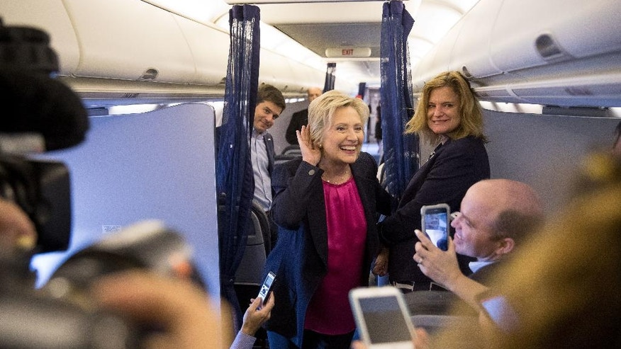 Democratic presidential candidate Hillary Clinton, accompanied by traveling press secretary Nick Merrill, left, and director of communications Jennifer Palmieri, right, listens to a question from a member of the media as her campaign plane prepares to take off at Westchester County Airport in Westchester, N.Y., Tuesday, Sept. 6, 2016, to head to Tampa for a rally in Tampa. (AP Photo/Andrew Harnik)