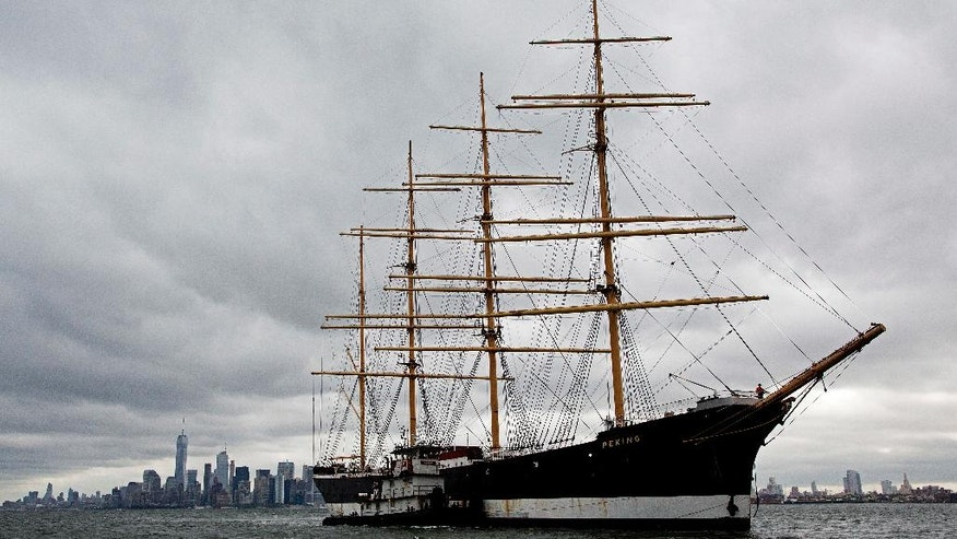 The Peking is escorted across New York Harbor by a team of tugboats en route to a dry dock on Staten Island, Wednesday, Sept. 7, 2016, in New York. The four-masted windjammer will eventually return it to its birthplace in Hamburg, Germany. (AP Photo/Mark Lennihan)