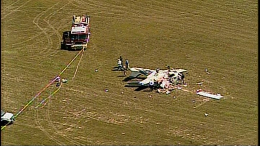Emergency crews survey wreckage after two planes collide in midair near a west Georgia airport.