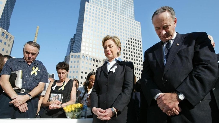 FILE - In this Sept. 11, 2003 file photo, then-Sen. Hillary Clinton, D-N.Y., center, and Sen. Charles Schumer, D-N.Y., right, bow their heads during a moment of silence as they join mourners gathering to remember those lost during the terrorist attacks on the World Trade Center at ground zero in New York. If Clinton wins the White House, Schumer is expected to be her top Democratic partner in the Senate, with the November election also determining whether he'll be leading a majority or minority party. In either case, their relationship would quickly become one of the most important in Washington, a crucial lynchpin in Clinton's efforts to garner congressional support for her priorities.  (Ruth Fremson/New York Times, Pool, File)