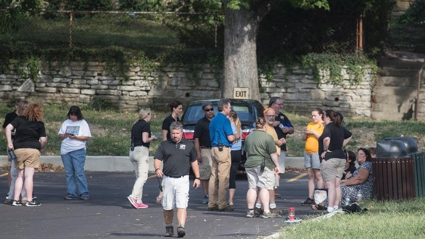 Cincinnati Zoo & Botanical Garden's employees stand in a nearby parking lot after the park was evacuated after a report of a suspicious package, Thursday, Sept. 8, 2016, in Cincinnati. (AP Photo/John Minchillo)