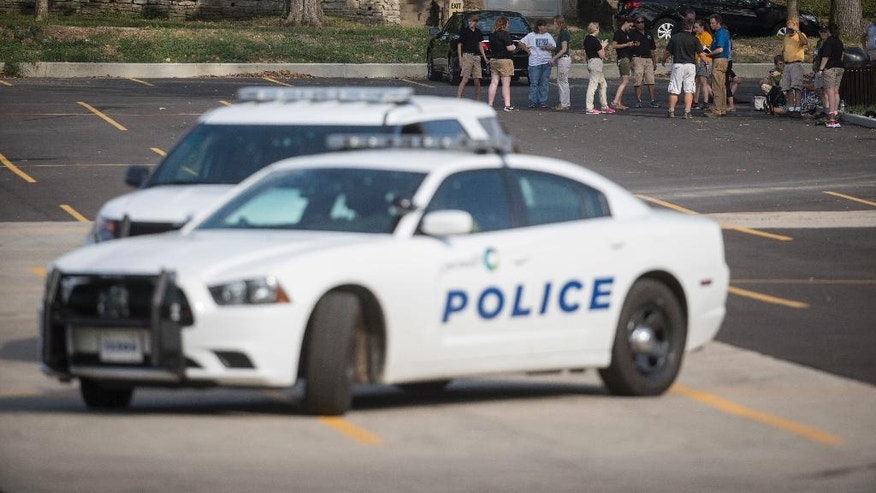Cincinnati Zoo & Botanical Garden's employees stand in a nearby parking lot beside police vehicles after the park was evacuated after a report of a suspicious package, Thursday, Sept. 8, 2016, in Cincinnati. (AP Photo/John Minchillo)