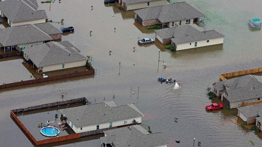 FILE- In this Saturday, Aug. 13, 2016 file aerial photo, a boat motors between flooded homes after heavy rains inundating the region, in Hammond, La. Eleven years ago, Hurricane Katrina exposed huge gaps in the disaster response plans of Louisiana and the nation. Lessons learned from that 2005 monster storm formed the backbone of state and federal reaction as flooding ravaged 20 Louisiana parishes last month. (AP Photo/Max Becherer, File)