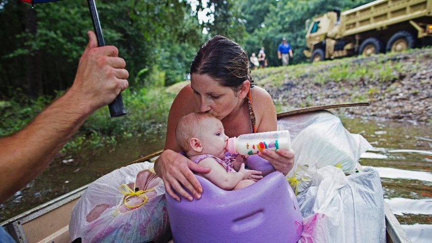 FILE - In this Sunday, Aug. 14, 2016 file photo, Danielle Blount kisses her 3-month-old baby Ember as she feeds her while they wait to be evacuated by members of the Louisiana Army National Guard near Walker, La., after heavy rains inundated the region. Eleven years ago, Hurricane Katrina exposed huge gaps in the disaster response plans of Louisiana and the nation. Lessons learned from that 2005 monster storm formed the backbone of state and federal reaction as flooding ravaged 20 Louisiana parishes last month.  (AP Photo/Max Becherer, File)
