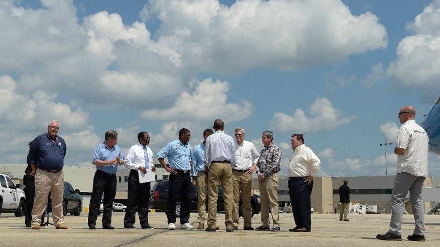 FILE - In this Tuesday, Aug. 23, 2016 file photo, President Barack Obama talks on the tarmac after arriving on Air Force One at Baton Rouge Metropolitan Airport in Baton Rouge, La. Obama is traveling to the area to survey the flood damage. FEMA Administrator Craig Fugate, Baton Rouge, La. Mayor Kip Holden, Rep. Cedric Richmond, D-La., Rep. Garret Graves, R-La., Sen. Bill Cassidy, R-La., Sen. David Vitter, R-La., and Louisiana Lt. Gov. Billy Nungesser, from left. Eleven years ago, Hurricane Katrina exposed huge gaps in the disaster response plans of Louisiana and the nation. Lessons learned from that 2005 monster storm formed the backbone of state and federal reaction as flooding ravaged 20 Louisiana parishes last month. (AP Photo/Susan Walsh, File)