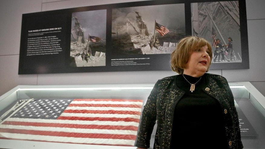 Shirley Dreifus, the original owner of the American flag, left, that firefighters hoisted at ground zero in the hours after the 9/11 terror attacks, speaks during an interview at the Sept. 11 museum, Thursday Sept. 8, 2016, in New York. After disappearing for more than a decade, the 3-foot-by-5-foot flag goes on display Thursday at the museum.  (AP Photo/Bebeto Matthews)