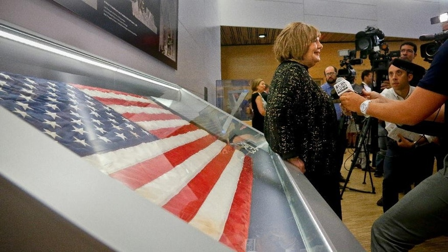 Shirley Dreifus, center, the original owner of the American flag, left, that firefighters hoisted at ground zero in the hours after the 9/11 terror attacks, hold interviews at the  Sept. 11 museum, Thursday Sept. 8, 2016, in New York. After disappearing for more than a decade, the 3-foot-by-5-foot flag goes on display Thursday at the museum.  (AP Photo/Bebeto Matthews)