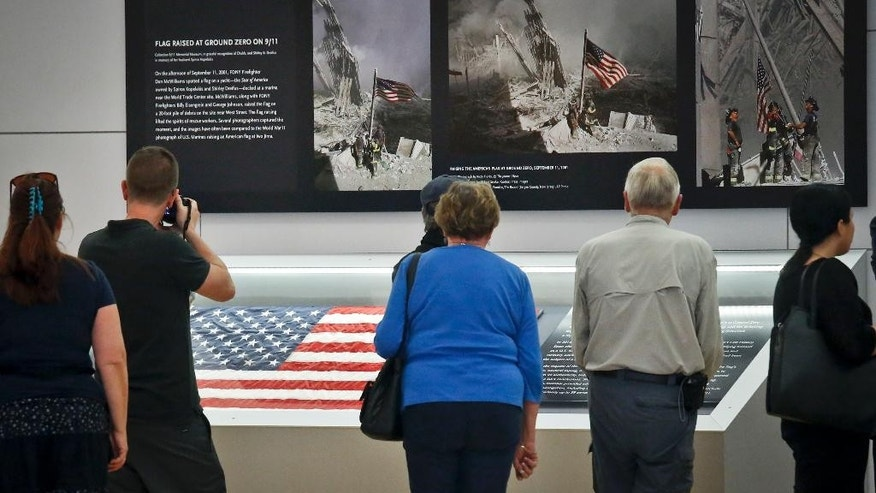 Visitors view the display for the American flag, left, that firefighters hoisted at ground zero in the hours after the 9/11 terror attacks, Thursday Sept. 8, 2016, at the Sept. 11 museum in New York. After disappearing for more than a decade the 3-foot-by 5-foot flag was donated to the museum after it was turned in two years ago by an as-yet-unidentified man at a firehouse in Everett, Wash.   (AP Photo/Bebeto Matthews)
