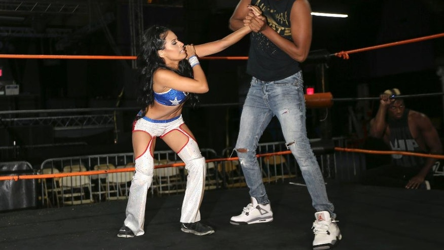 """Thea Trinidad practices her wrestling moves with Isiah Kassidy at a ring in New York on Friday, Aug. 19, 2016. Her father, Michael, was a former high school wrestler who didn't flinch when his tomboy daughter did leaping moves off the furniture. In fact, """"he'd say, 'No, you're doing it wrong _ let me show you,'"""" says Thea, 25, who lives in Tampa, Fla. She says she feels her father's spirit every time she goes into the ring. """"This one's for you, Dad,"""" she tells herself. """"Protect me out there."""" (AP Photo/Seth Wenig)"""