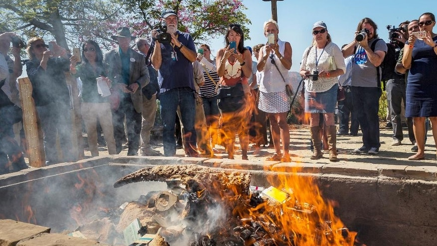 In this photo provided by the San Diego Zoo Safari Park, flames consume confiscated rhinoceros horn items in a fire pit at the Park in Escondido, Calif., Thursday, Sept. 8, 2016. Officials burned the items with an estimated black market value of $1 million in a symbolic gesture to show the United States is committed to ending illegal wildlife trafficking. The U.S. Fish and Wildlife Service partnered with the zoo and California Department of Fish and Wildlife to hold the massive bonfire of items. (Ken Bohn/San Diego Zoo Safari Park via AP)