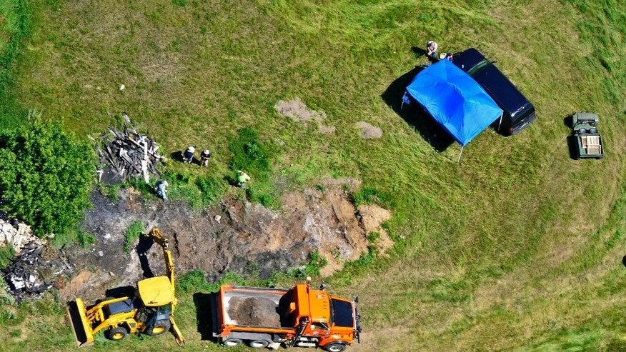 FILE - In this June 1, 2010 file photo, investigators use a tractor-mounted backhoe to dig for evidence just southeast of the Rassier farm in St. Joseph, Minn., near the site where 11-year-old Jacob Wetterling was abducted in 1989. Dan Rassier, who lived under a cloud of suspicion since Jacob was kidnapped, can finally breathe easier now that another man has confessed to the boy's abduction and murder. Rassier was questioned several times over the years and in 2010 named a person of interest, with authorities digging for evidence on his family farm. On Sept. 6, 2016, Danny Heinrich confessed to the killing. (Kimm Anderson/St. Cloud Times via AP, File)