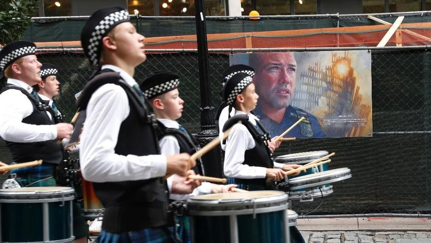 A marching band passes artwork depicting a fallen New York City police officer as they march during the NYPD Emerald Society Pipes & Drums memorial procession, Friday, Sept. 9, 2016, in New York. (AP Photo/Mary Altaffer)