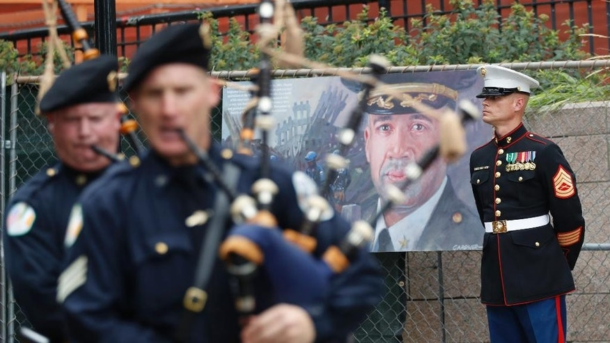 A member of the United States Marine Corp. stands guard next to artwork depicting a fallen New York City police officer as bagpipers march during the NYPD Emerald Society Pipes & Drums memorial procession, Friday, Sept. 9, 2016, in New York. (AP Photo/Mary Altaffer)