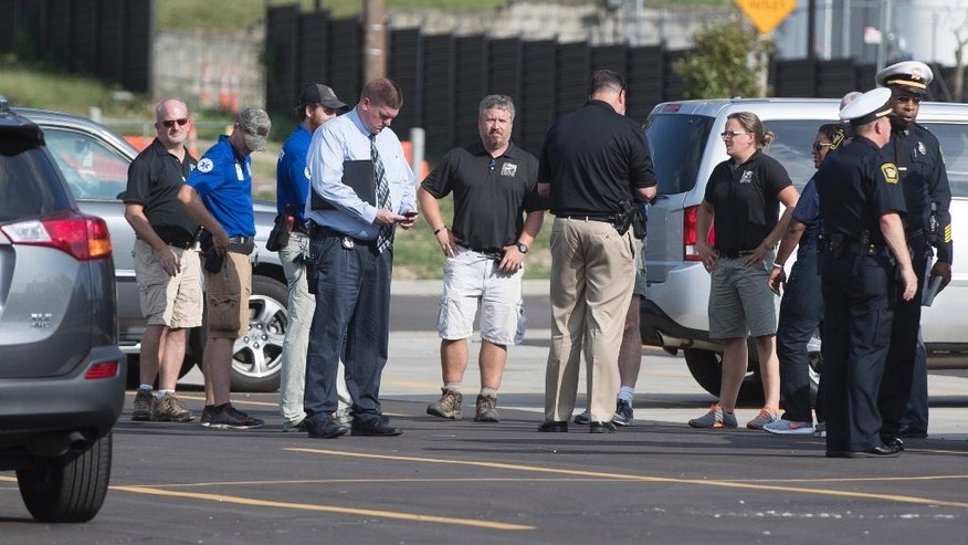 Cincinnati Zoo & Botanical Garden's employees meet with authorities in a nearby parking lot after the park was evacuated after a report of a suspicious package, Thursday, Sept. 8, 2016, in Cincinnati. (AP Photo/John Minchillo)