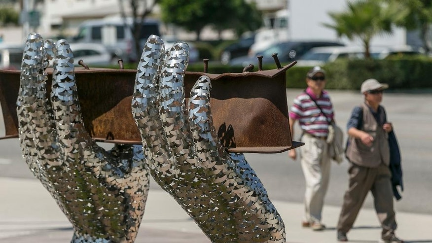 """In this Friday, Aug. 26, 2016 photo, pedestrians walk by artist Heath Satow's sculpture """"Reflect,"""" made with a damaged, rusted I-beam from the collapsed World Trade Center buildings, outside the Rosemead, Calif., city hall plaza. The 9/11 memorial sculpture has 2,976 interlocking birds representing individual victims from the 2001 attacks. (AP Photo/Damian Dovarganes)"""