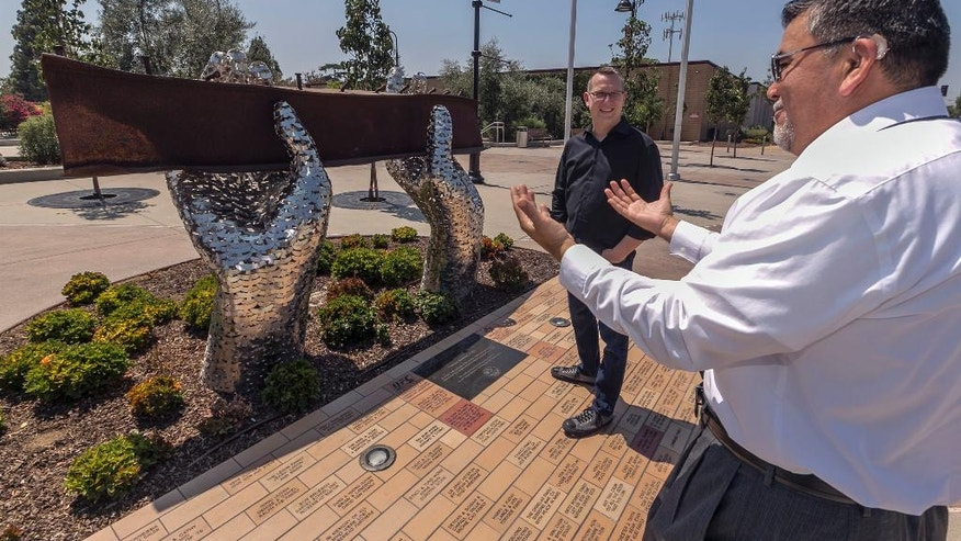 "In this Friday, Aug. 26, 2016 photo, California State EDD employee Juan Milan, right, talks with artist Heath Satow about his sculpture, ""Reflect,"" made with a damaged, rusted I-beam from the collapsed World Trade Center buildings, outside the Rosemead, Calif., city hall plaza. Satow said he purposely positioned the beam at about eye level, so people could see, touch and feel it. (AP Photo/Damian Dovarganes)"