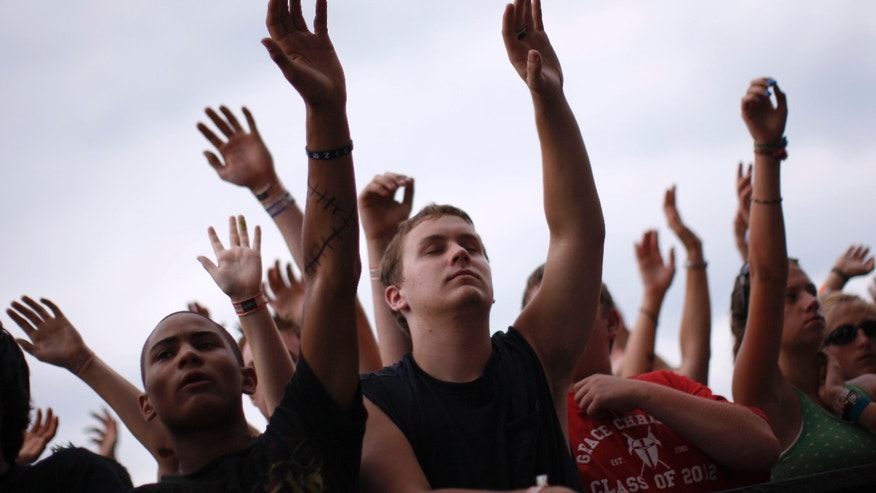 People in the crowd raise their hands together in worship as they listen to the band The Afters at the Creation Christian music festival near Mount Union, Pennsylvania in 2008.