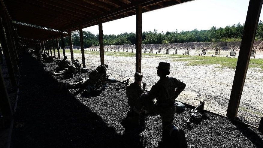 In this photo taken Wednesday, Aug. 17, 2016 a U.S. Army drill sergeant kneels while overlooking recruits during live-fire marksmanship training at Fort Jackson, S.C.  As gun ownership among young Americans drops and the Army trains a new generation more accustomed to blasting out emojis on cellphones than taking aim at targets, drill sergeants are confronting a new challenge: More than half of raw recruits have never held, let alone fired, a weapon. (AP Photo/Gerry Broome)