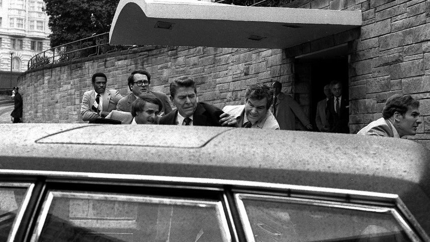 FILE - In this March 30, 1981 file photo, U.S. President Ronald Reagan, center, is shown being shoved into the President's limousine by secret service agents after being shot outside a Washington hotel. The man who shot Reagan is scheduled to leave a Washington mental hospital for good on Saturday, Sept. 10, 2016, more than 35 years after the shooting. A federal judge ruled in late July that the 61-year-old John Hinckley Jr. is not a danger to himself or the public and can live full-time at his mother's home in Williamsburg, Virginia. (AP Photo/Ron Edmonds, File)
