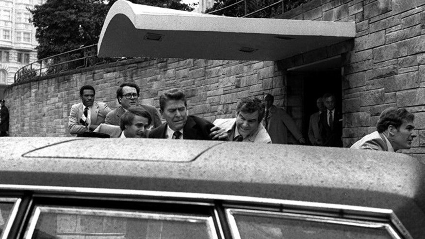 FILE - In this March 30, 1981 file photo, U.S. President Ronald Reagan is shown being shoved into the President's limousine by secret service agents after being shot outside a Washington hotel.  Secret service agent Jerry Parr, in raincoat to the right of Reagan, who pushed Reagan into the limousine, was credited with saving President Ronald Reagan's life on the day he was shot, has died. He was 85. (AP Photo/Ron Edmonds)