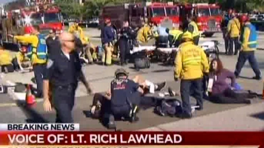 """FILE - In this Dec. 2, file image from video provided by KNBC-TV, first responders attend to people outside a Southern California social services center in San Bernardino, where one or more gunmen opened fire, shooting multiple people. A lengthy report into the San Bernardino terror attack reveals new details about the killings last year and the way the husband and wife who carried them out died in a police shootout. The report released Friday, Sept. 9, 2016 provides an in-depth look at the chaos and confusion as the Islamic extremists opened fire at a meeting of the man's colleagues. The carnage was described as looking """"like a bomb had gone off."""" (KNBC-TV via AP, File) MANDATORY CREDIT. TV OUT"""