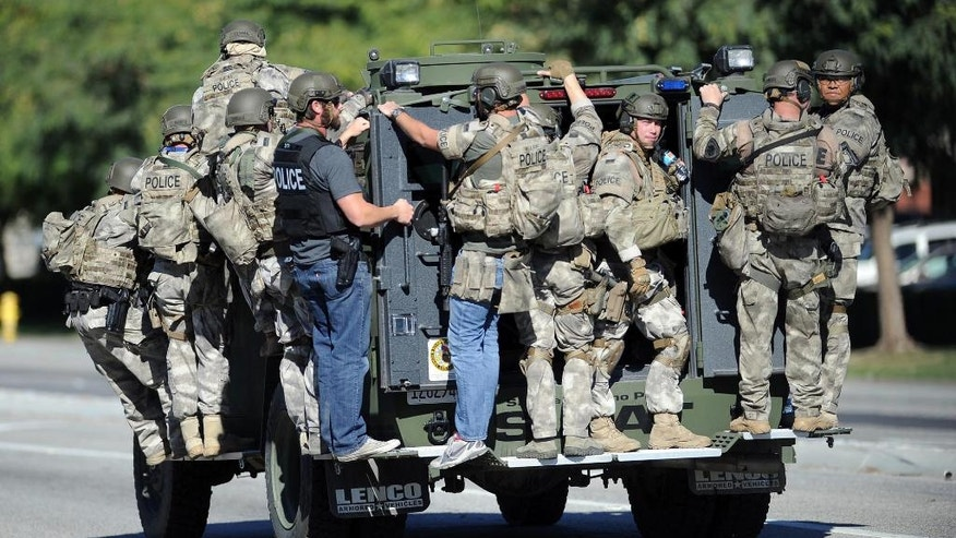 """FILE - In this Dec. 2, 2015 file photo, an armored vehicle carries police officers near the scene of multiple shootings in San Bernardino, Calif. A lengthy report into the San Bernardino terror attack reveals new details about the killings last year and the way the husband and wife who carried them out died in a police shootout. The report released Friday, Sept. 9, 2016, provides an in-depth look at the chaos and confusion as the Islamic extremists opened fire at a meeting of the man's colleagues. The carnage was described as looking """"like a bomb had gone off."""" (Micah Escamilla/Los Angeles News Group via AP, File)"""