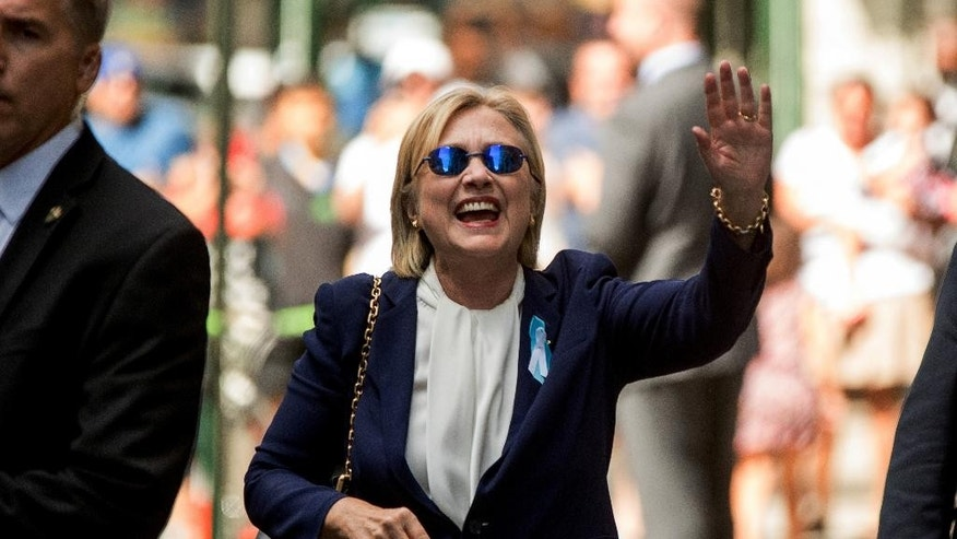 "Democratic presidential candidate Hillary Clinton waves after leaving an apartment building Sunday, Sept. 11, 2016, in New York. Clinton's campaign said the Democratic presidential nominee left the 9/11 anniversary ceremony in New York early after feeling ""overheated."" (AP Photo/Andrew Harnik)"