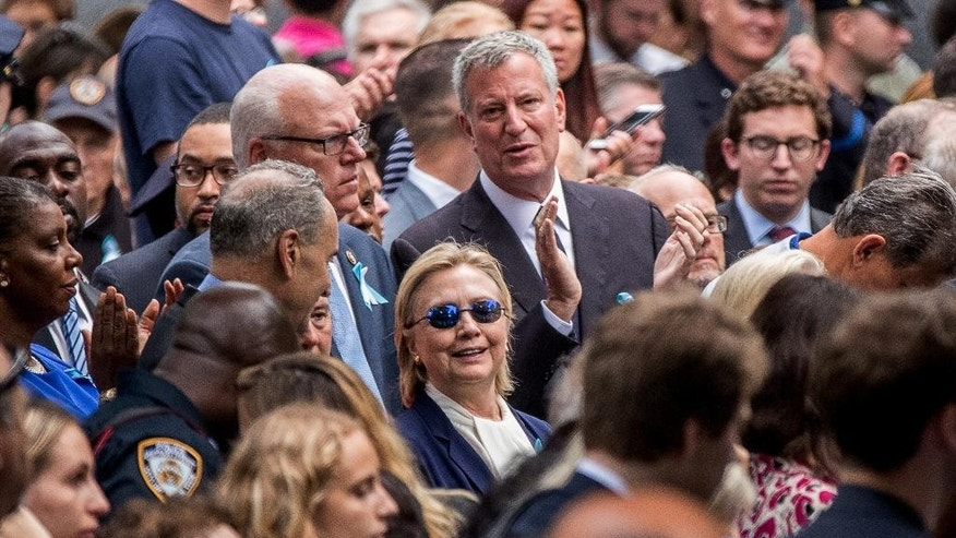 Democratic presidential candidate Hillary Clinton, center, accompanied by Sen. Chuck Schumer, D-N.Y., center left, Rep. Joseph Crowley, D-N.Y., second from left, and New York Mayor Bill de Blasio, center top, attends a ceremony at the Sept. 11 memorial, in New York, Sunday, Sept. 11, 2016. (AP Photo/Andrew Harnik)