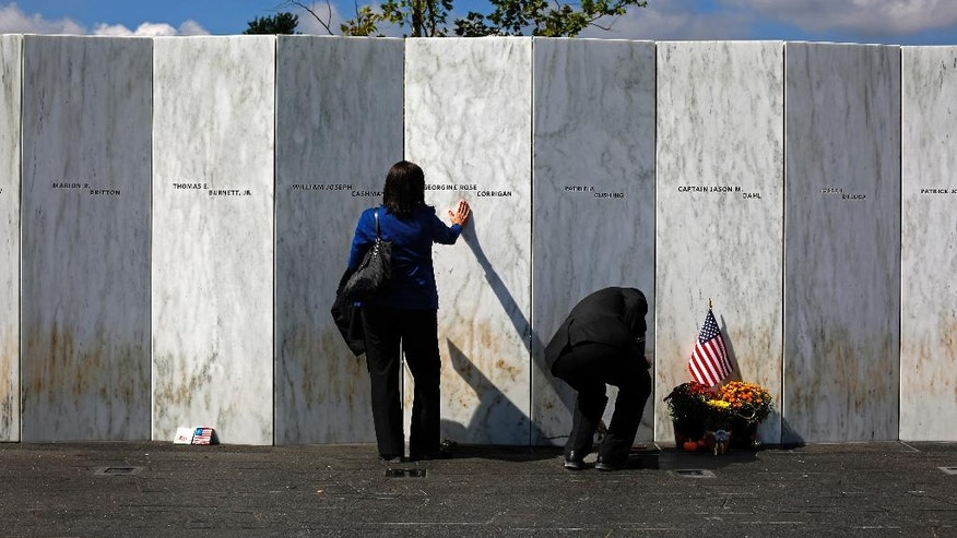 FILE- In this Sept. 11, 2015 file photo, a visitor pauses at the Wall of Names after a Service of Remembrance at the Flight 93 National Memorial in Shanksville, Pa. Victims' relatives and dignitaries will convene Sunday, Sept. 11, 2016, at the site for one of the constants in how America remembers 9/11 after 15 years, the anniversary ceremony itself. (AP Photo/Gene J. Puskar, File)